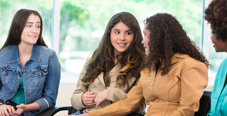 Beautiful Hispanic mom pats her teen daughter's leg while talking in a group therapy session.